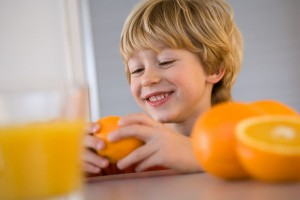 Young Boy Eating Oranges